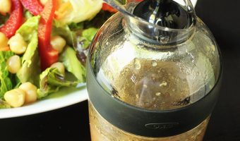 cruet with italian salad dressing next to green salad