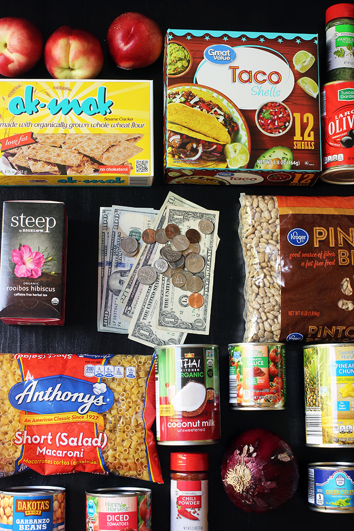 flatlay of groceries and cash on black tabletop