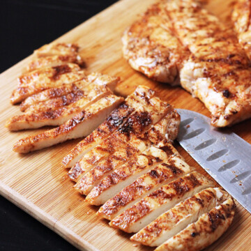 grilled chicken breasts sitting on top of a wooden cutting board