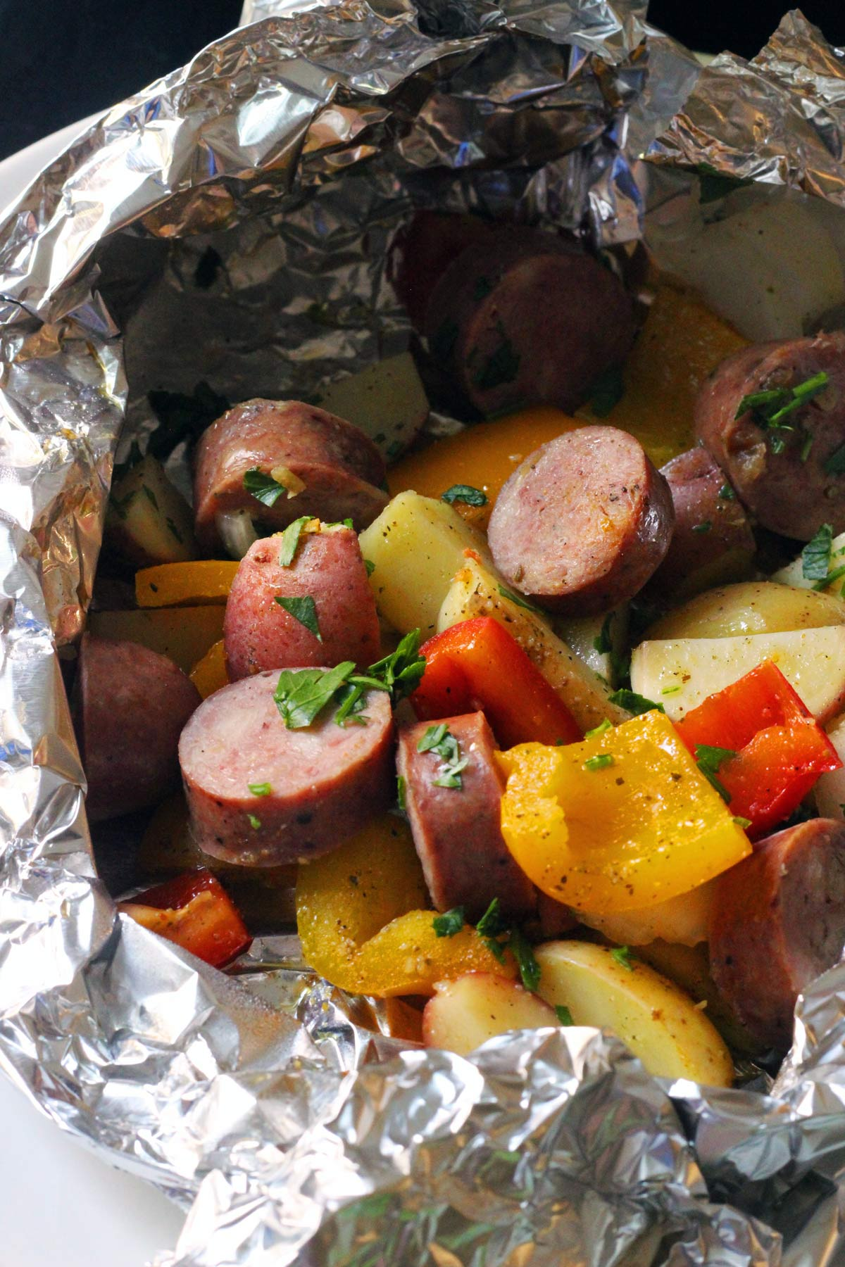 open foil packet of peppers, onions, and sausage.