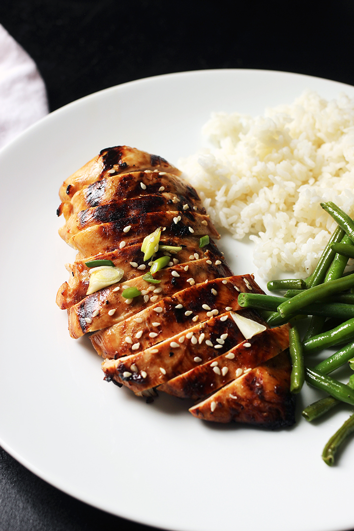 white dinner plate with asian chicken rice and green beans