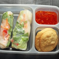 A plastic container with cookies and summer rolls