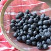 washed blueberries in fine mesh strainer on red cloth