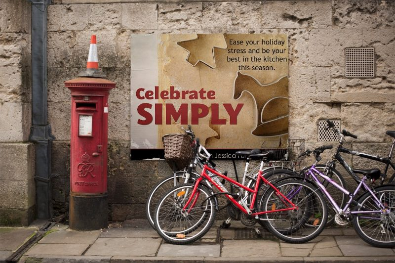 bicycle on city street next to poster of celebrate simply