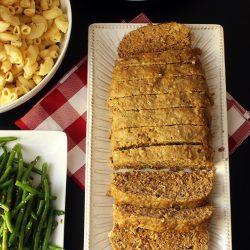 platter of sliced meatloaf next to side dishes