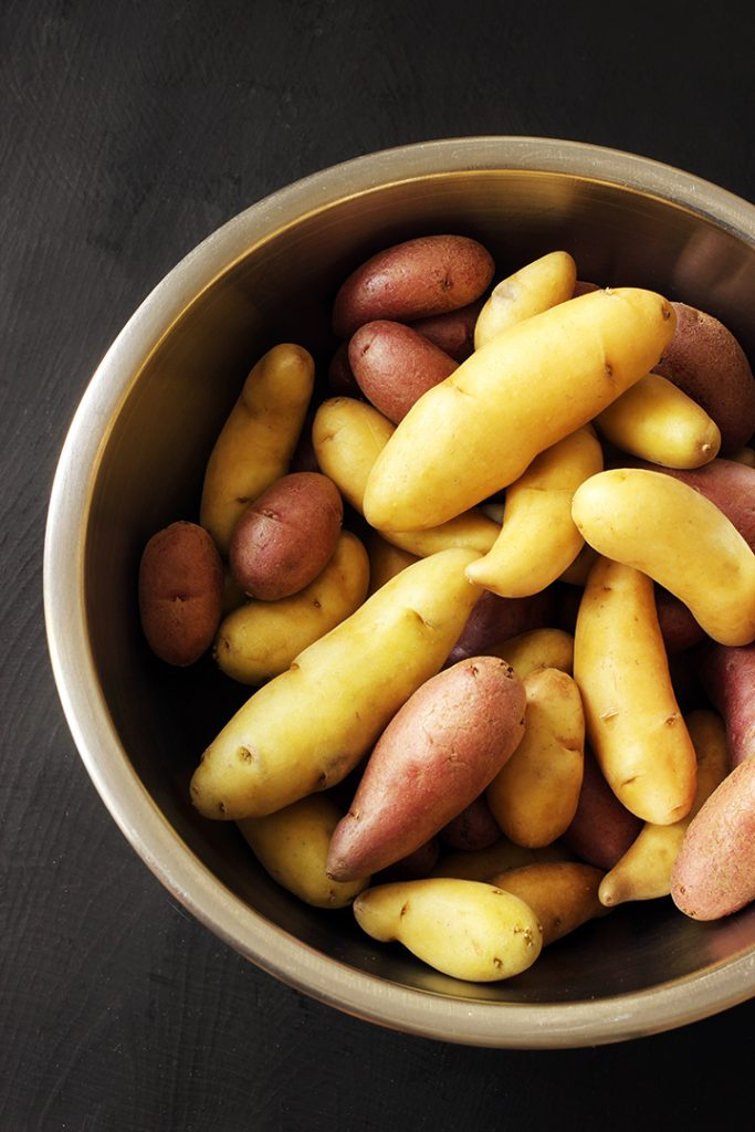 purple and yellow fingerling potatoes in a metal bowl