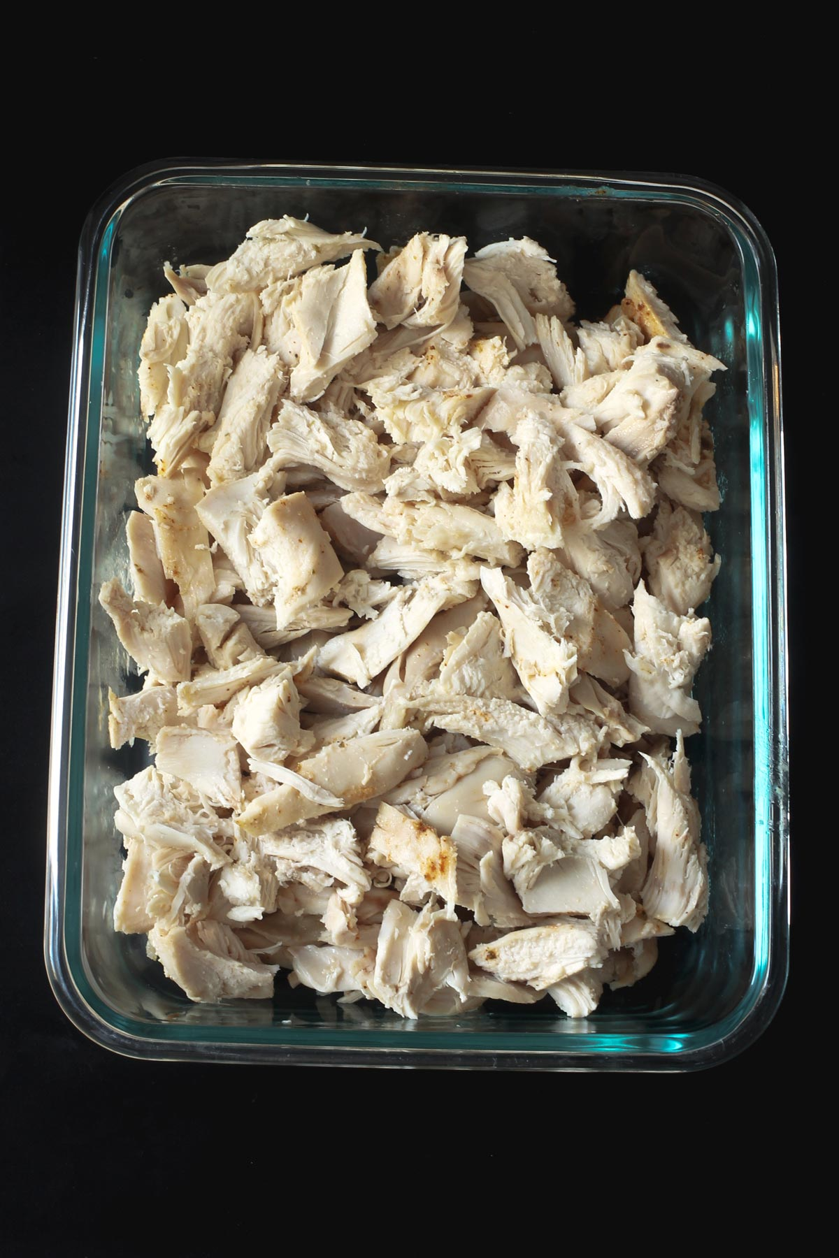 glass dish with cubed chicken cooked in the slow cooker ready for recipes.