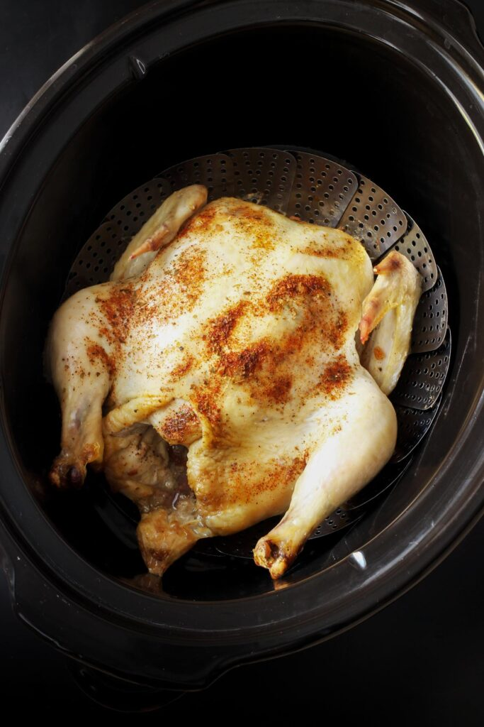 a whole chicken cooked in the crockpot sitting on a rack in the crock.