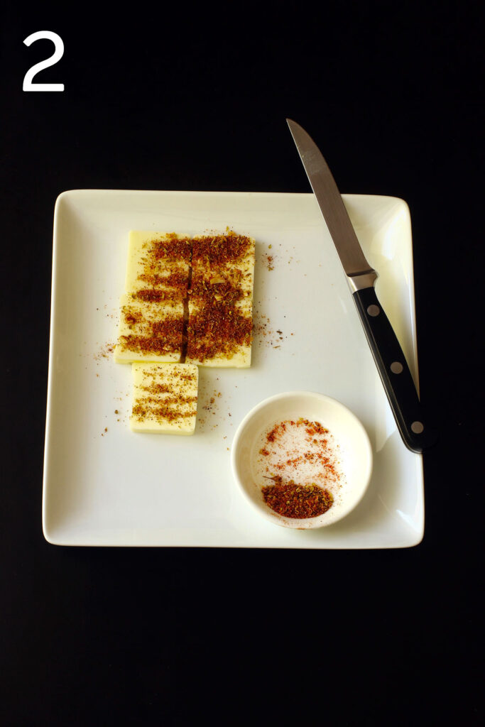 butter on square plate cut into pats and coated with seasoned salt.
