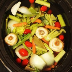 vegetables floating in water in slow cooker
