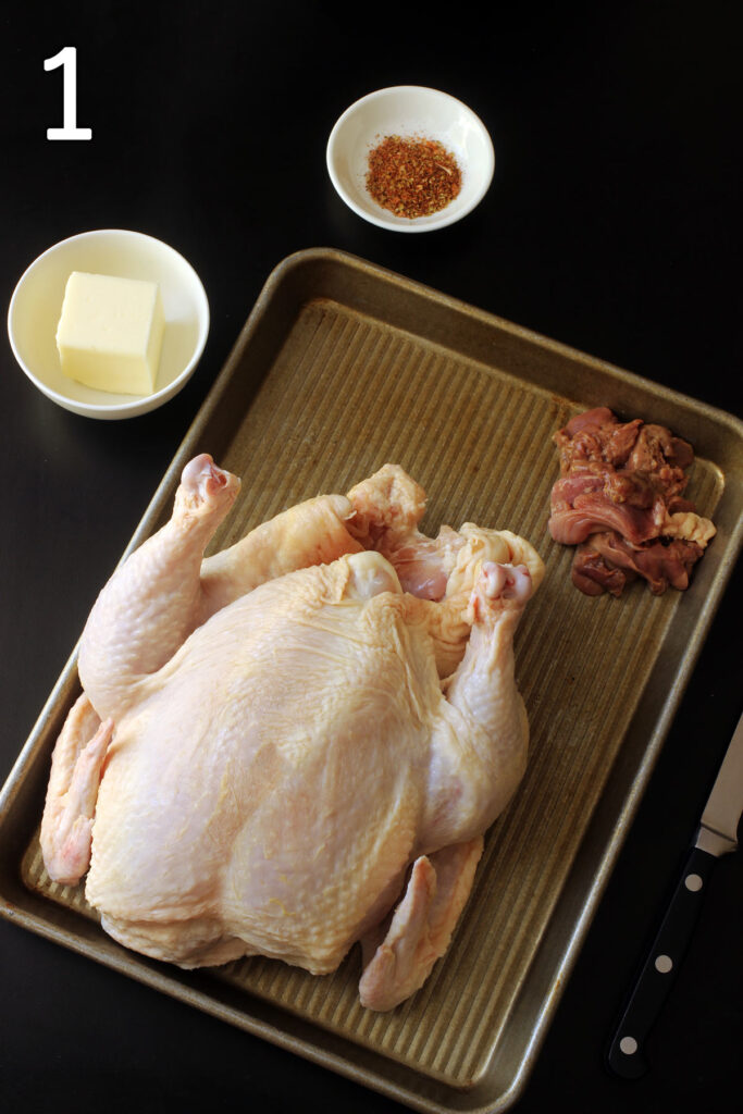 whole chicken on tray with giblets in the corner of the tray.