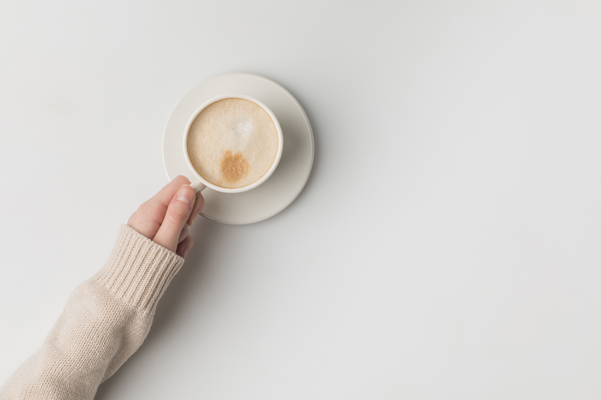 A close up of a hand holding a capuccino