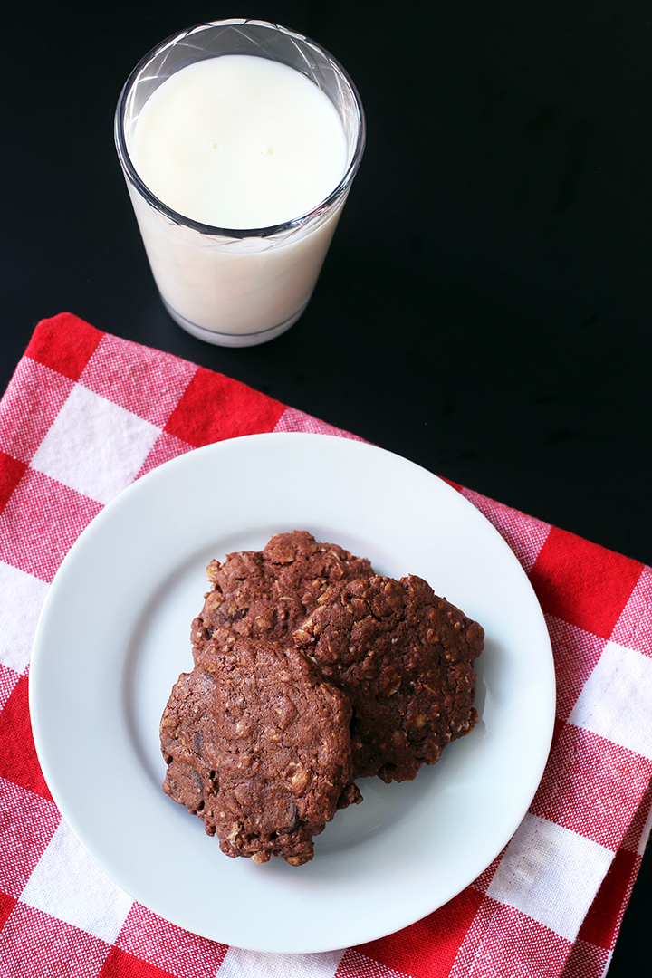 chocolate oatmeal cookies on a white plate with red checked napkin and glass of milk