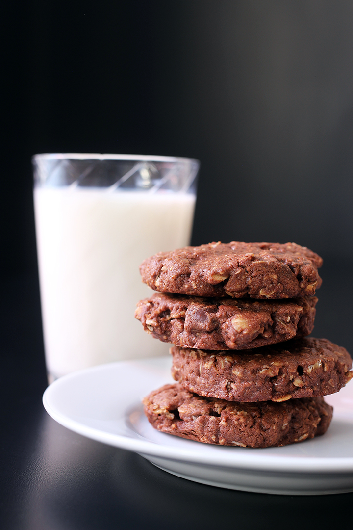 stack of chocolate oatmeal cookies on white plate with glass of milk
