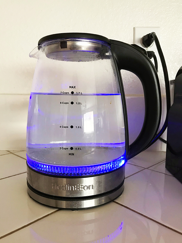 glass water kettle turned on with blue light