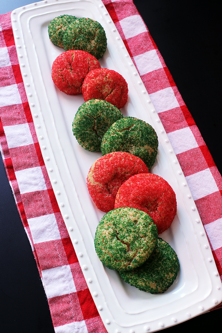 green and red sugar cookies on platter on red checked cloth