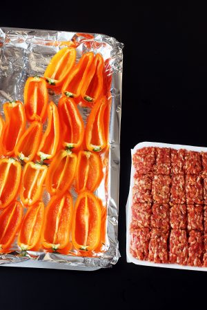 A tray of hollowed peppers next to a tray of portioned sausage