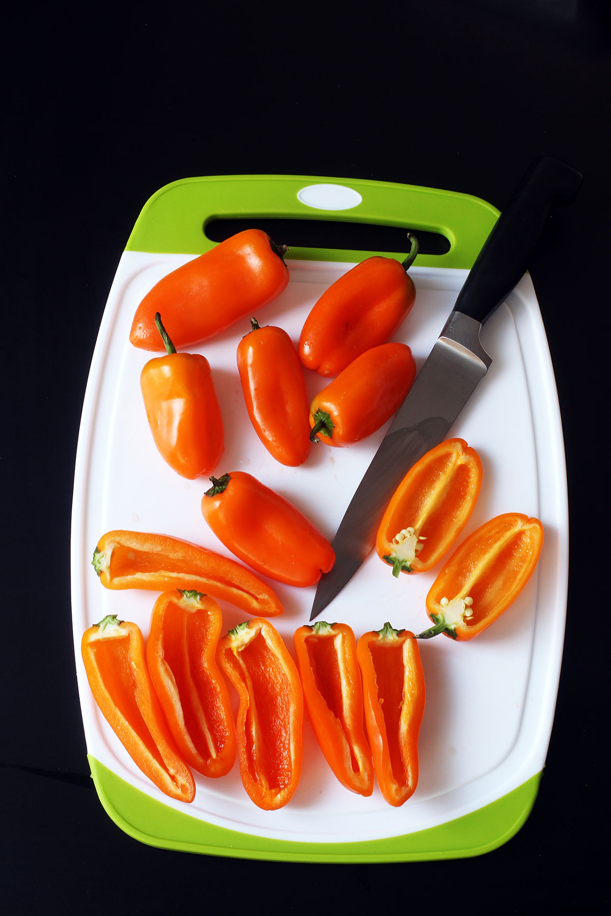 mini peppers on cutting board with knife