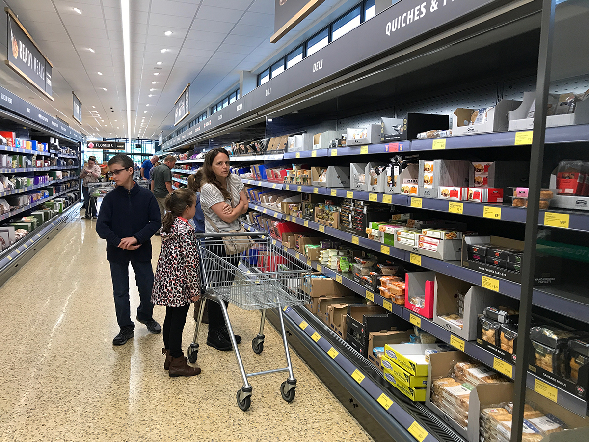 mom and kids with empty grocery cart in uk aldi grocery store