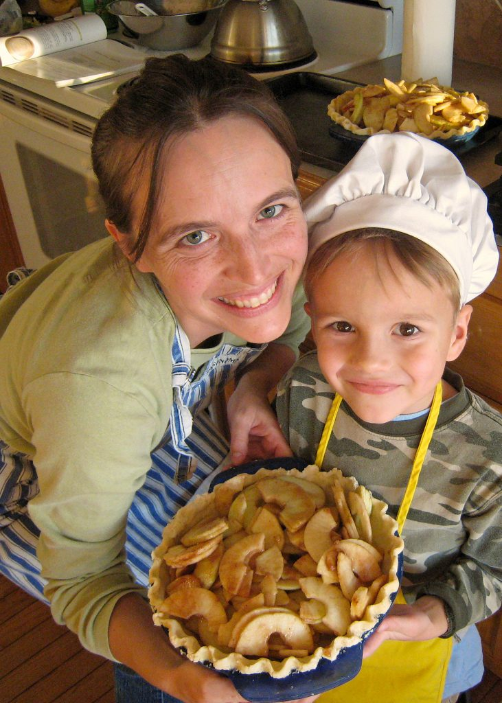 mother and boy holding apple pie they made together