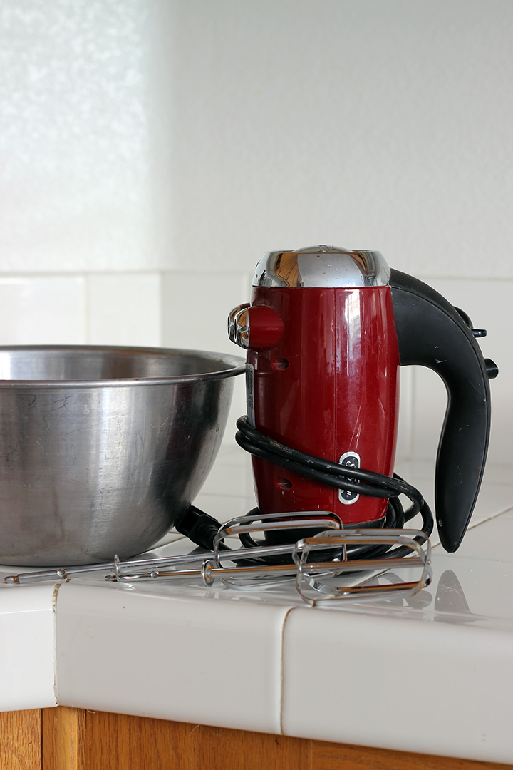 red hand mixer and beaters next to stainless bowl on counter