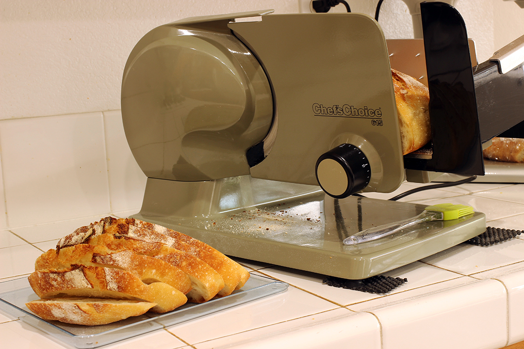 slicing sourdough bread on food slicer