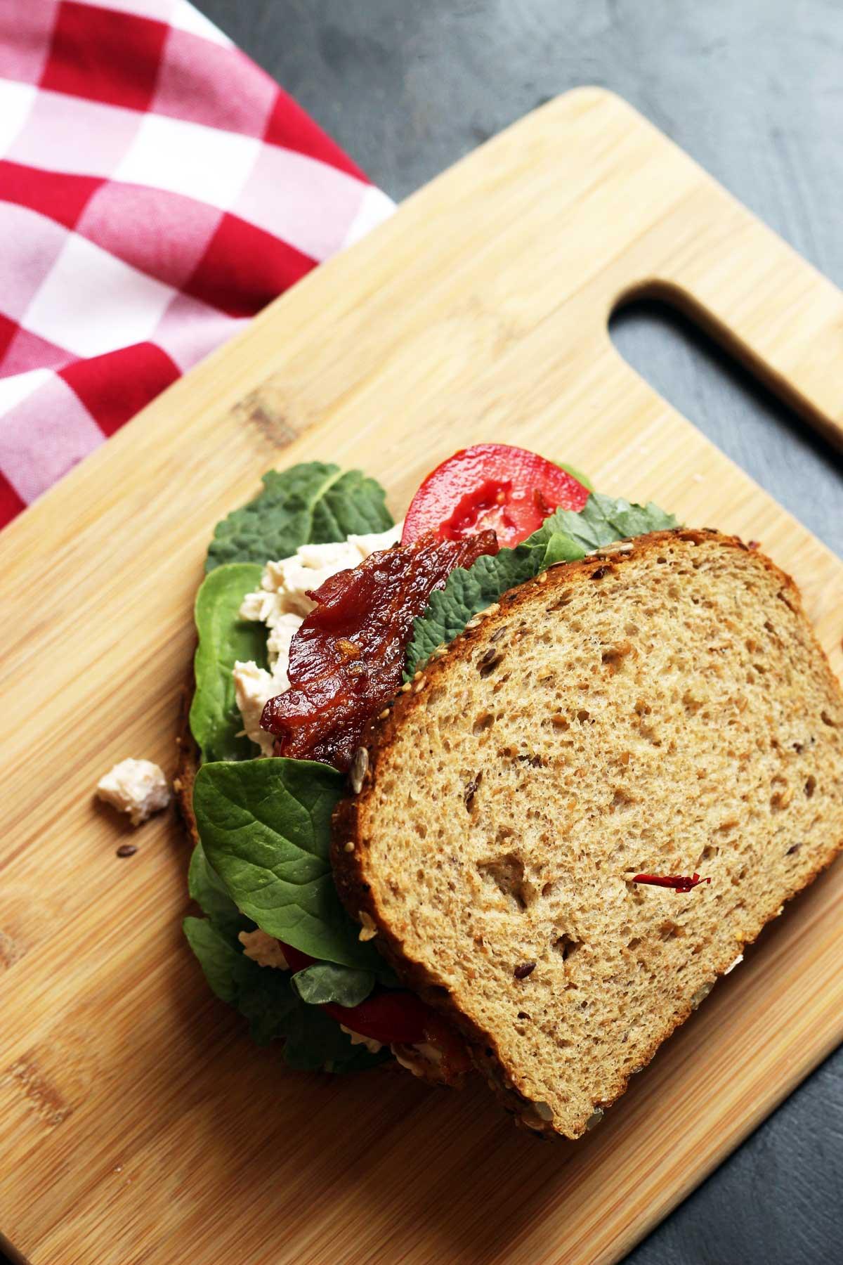 chicken salad BLT sandwich on wooden cutting board
