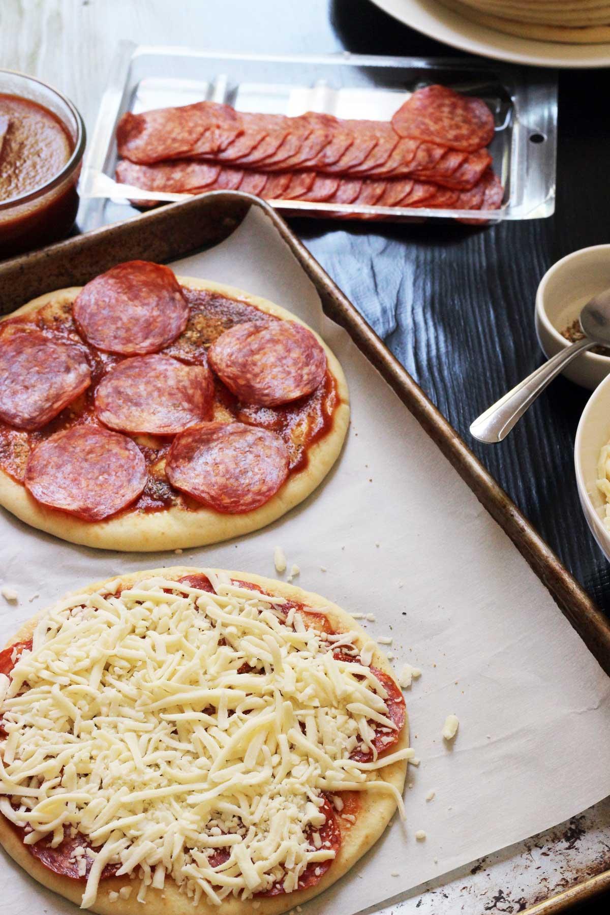 assembling pita bread pizzas on tray