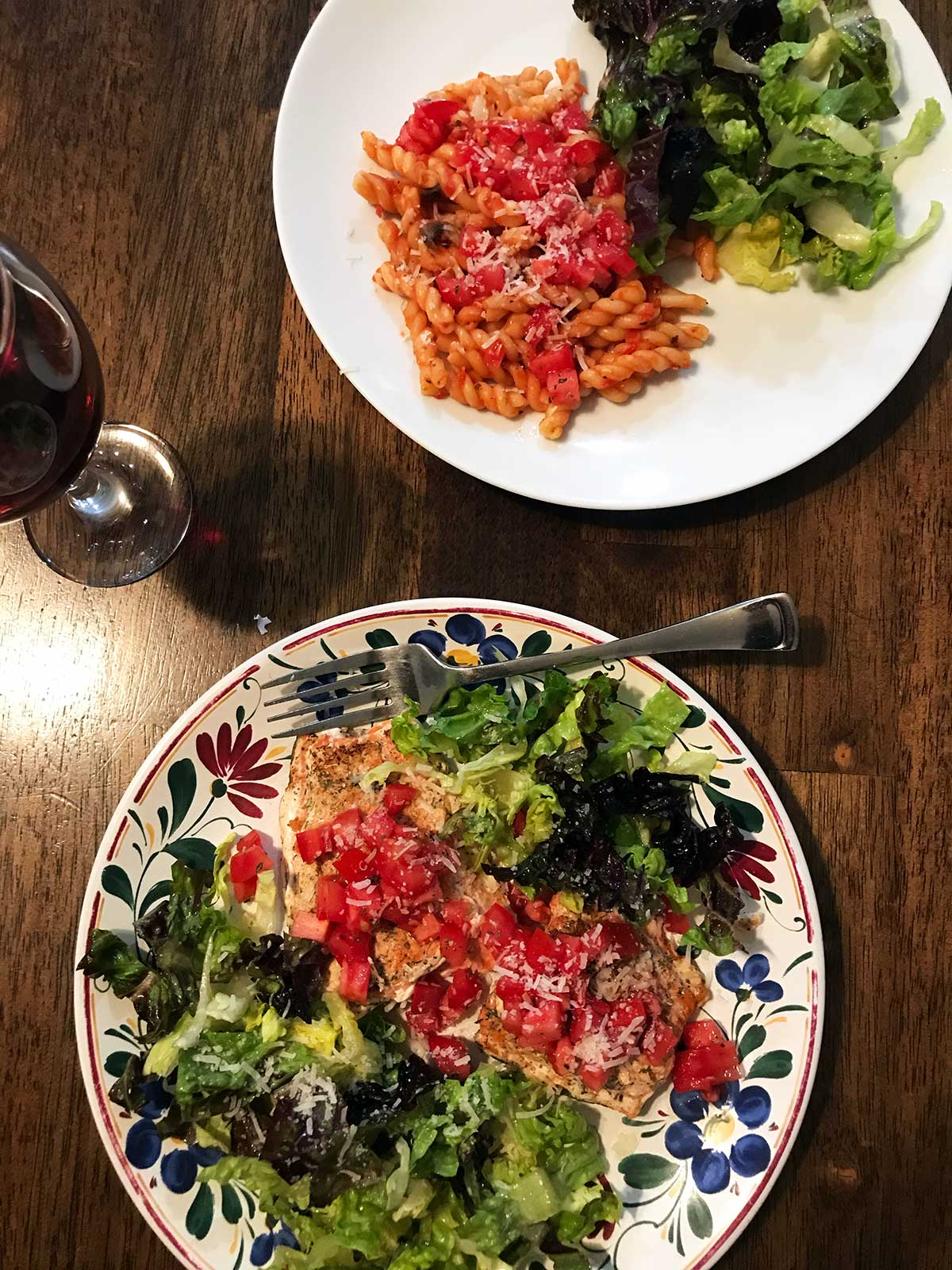 dinner plates of pasta with glass of wine