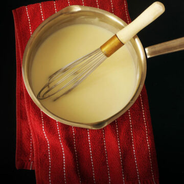 saucepan of white sauce on a red striped towel with a whisk.