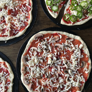 unbaked pizzas on screens on table