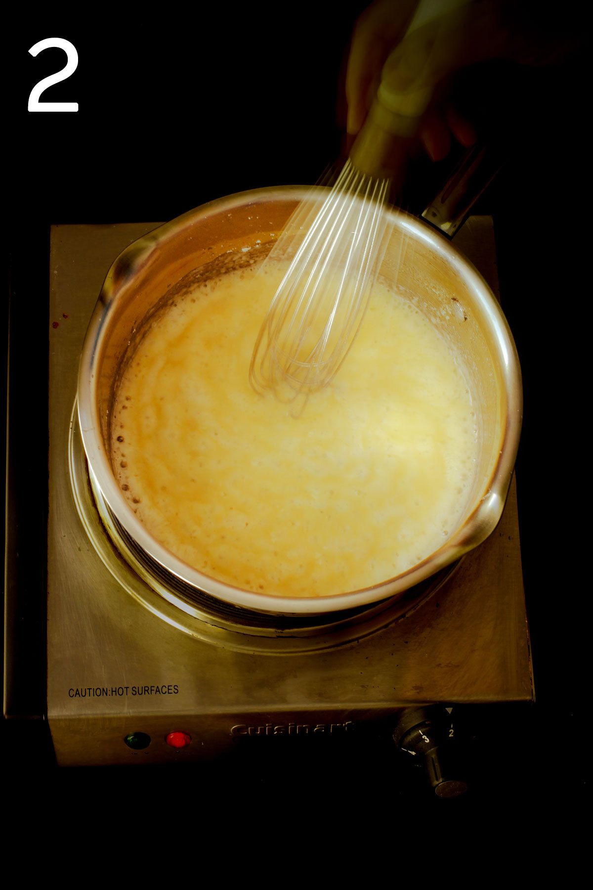 whisking in the milk to the roux in saucepan.