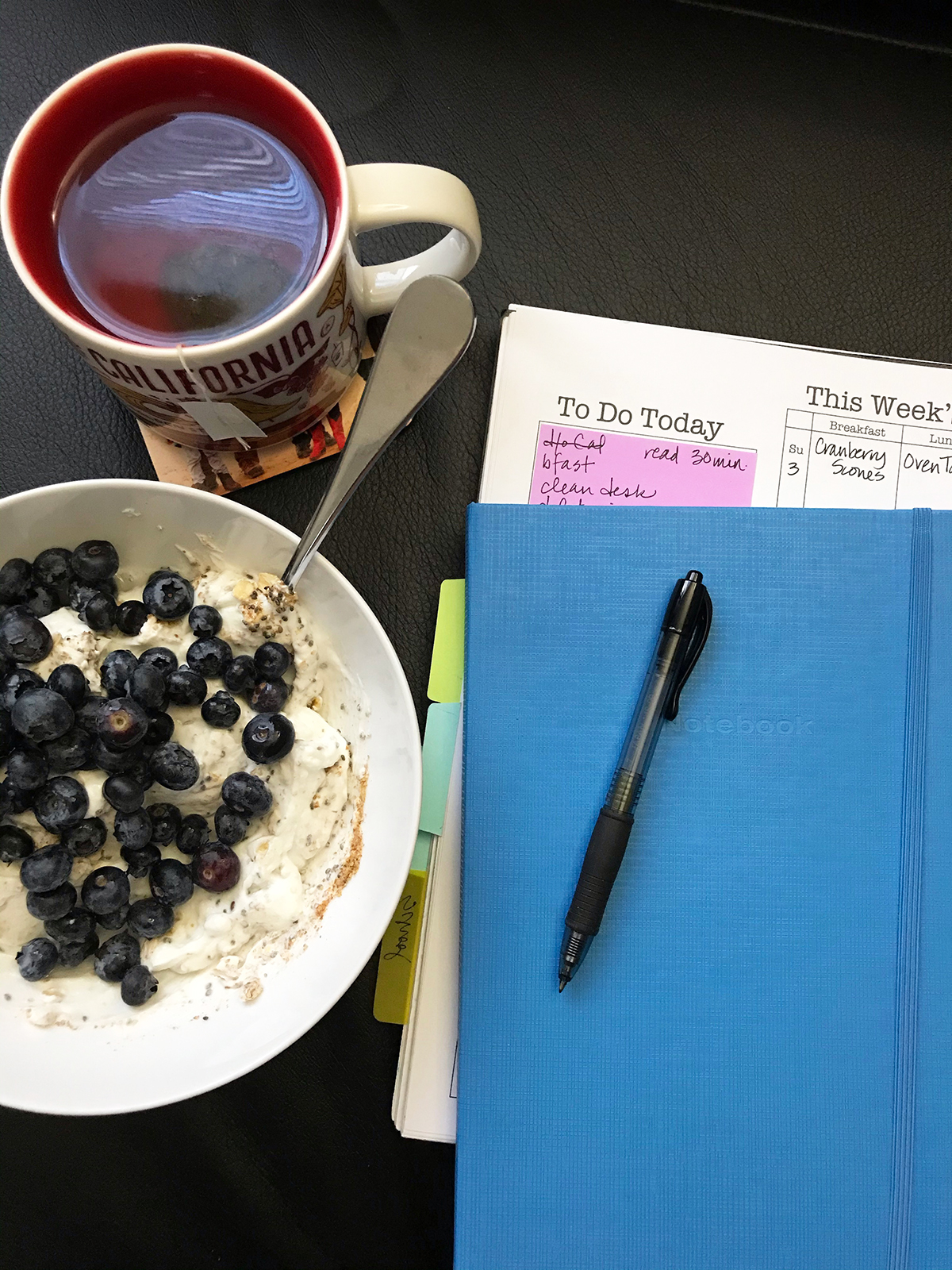 yogurt and berries tea and planner and pen