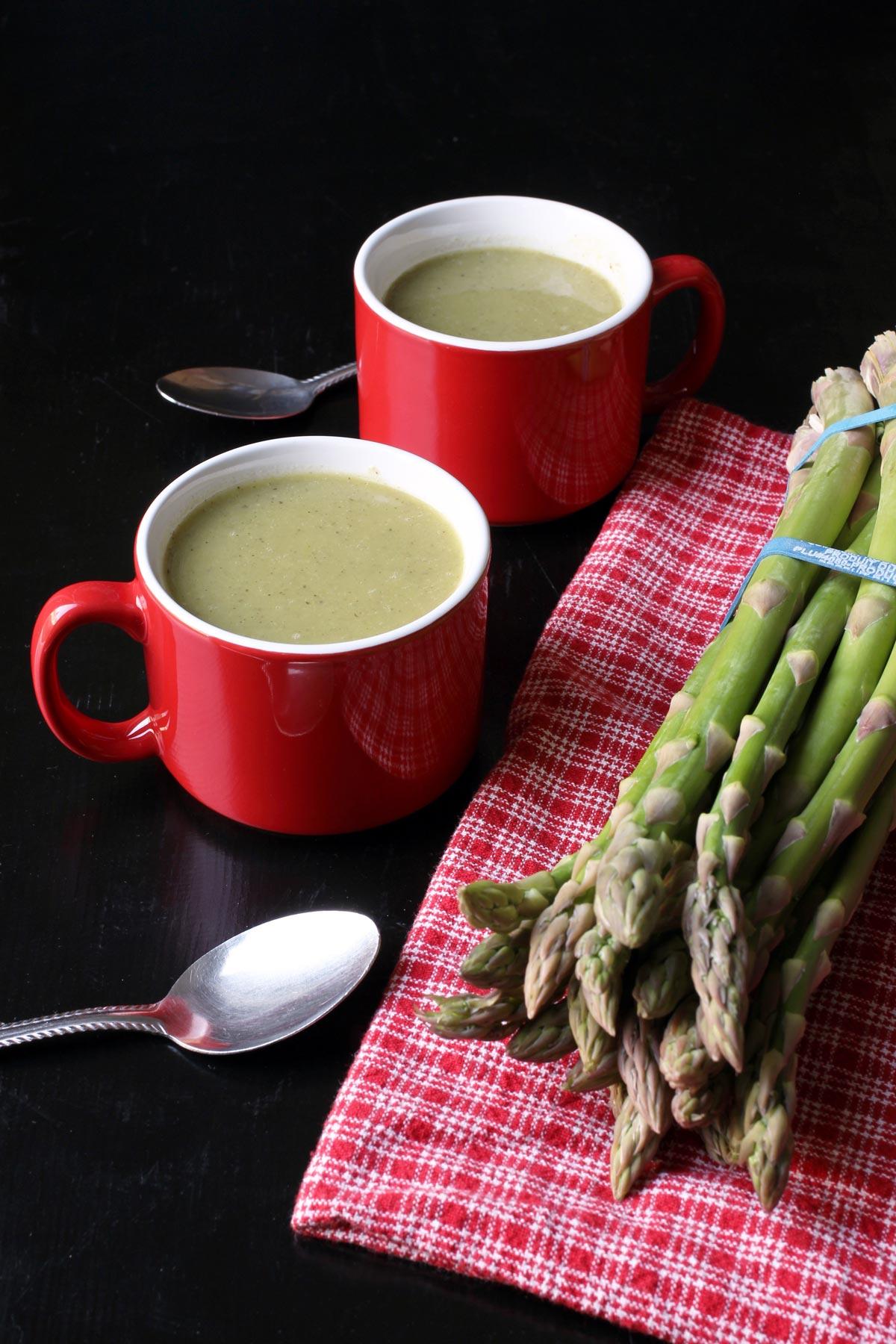 asparagus next to mugs of soup