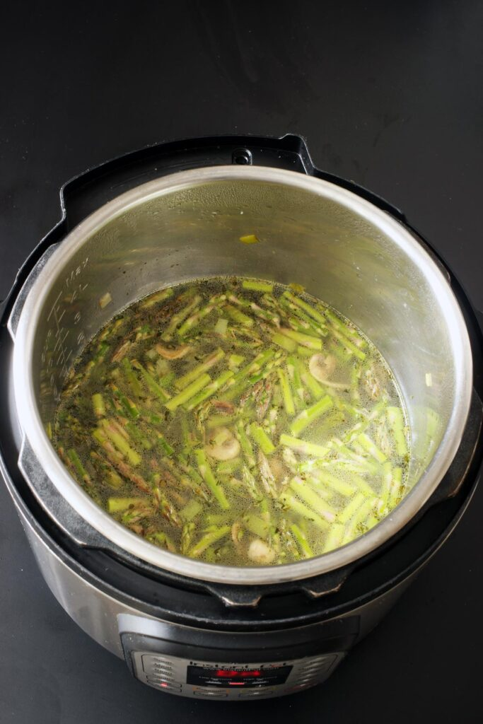 adding water, potato, and asparagus to soup