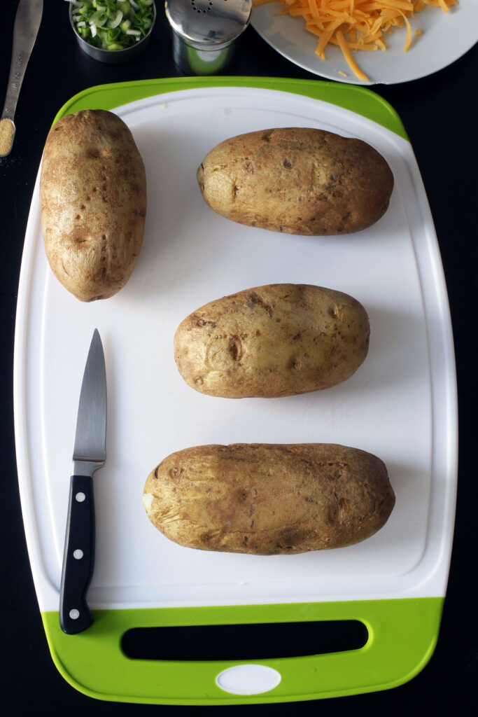 baked potatoes on board with knife