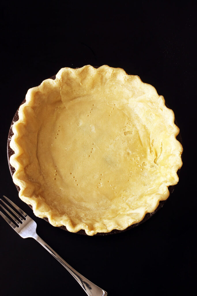 half baked pie crust with fork