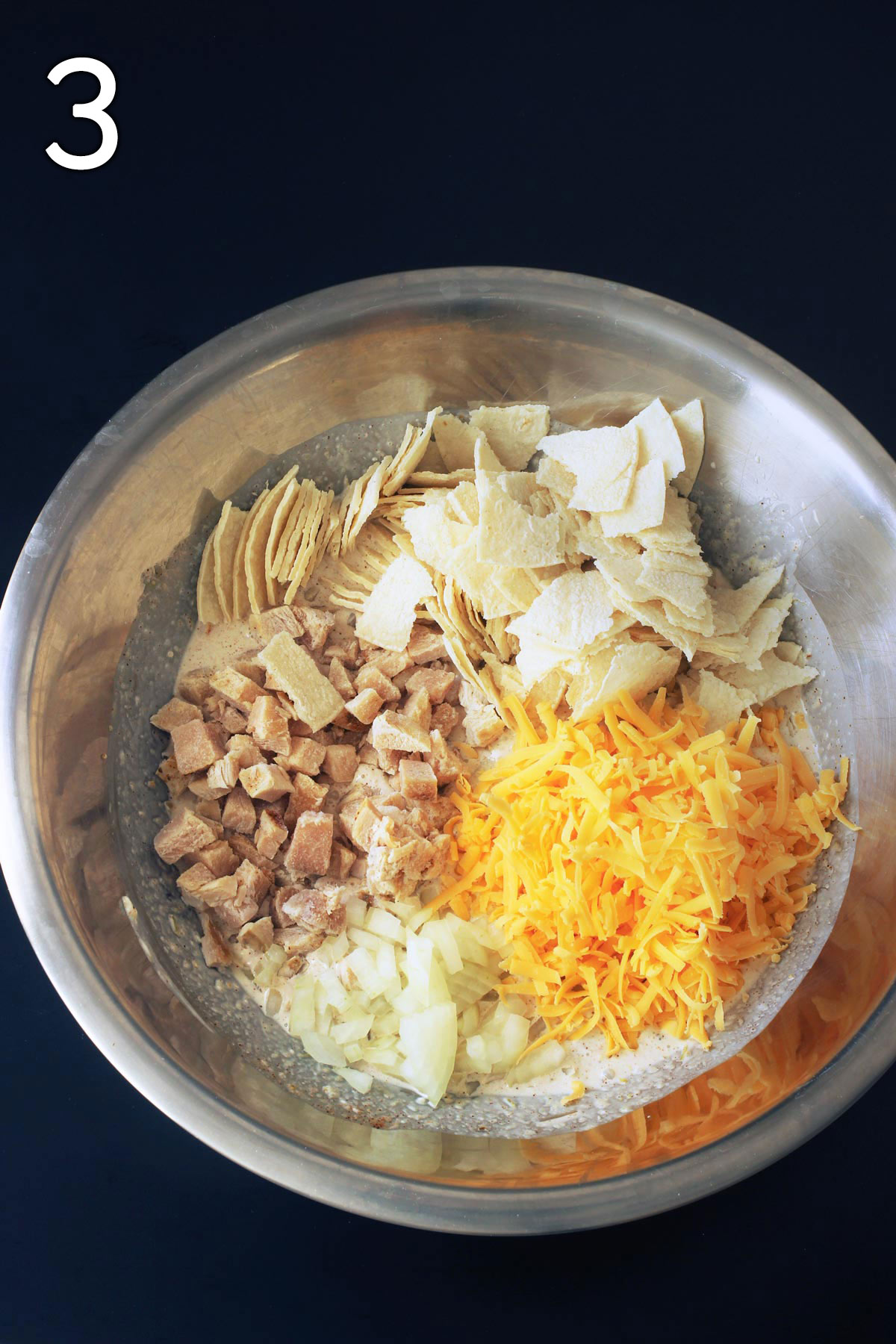 adding the chicken, tortillas, cheese, and onion to the sauce in the mixing bowl.