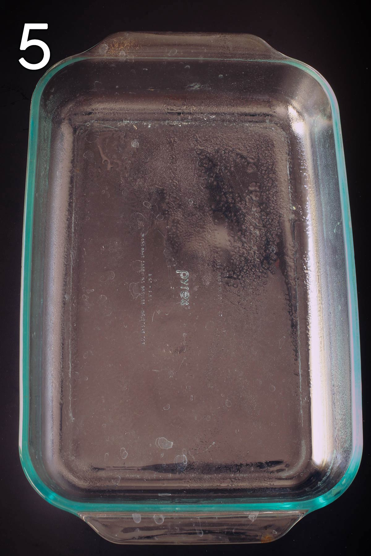 greased 9x13-inch baking dish on black tabletop.