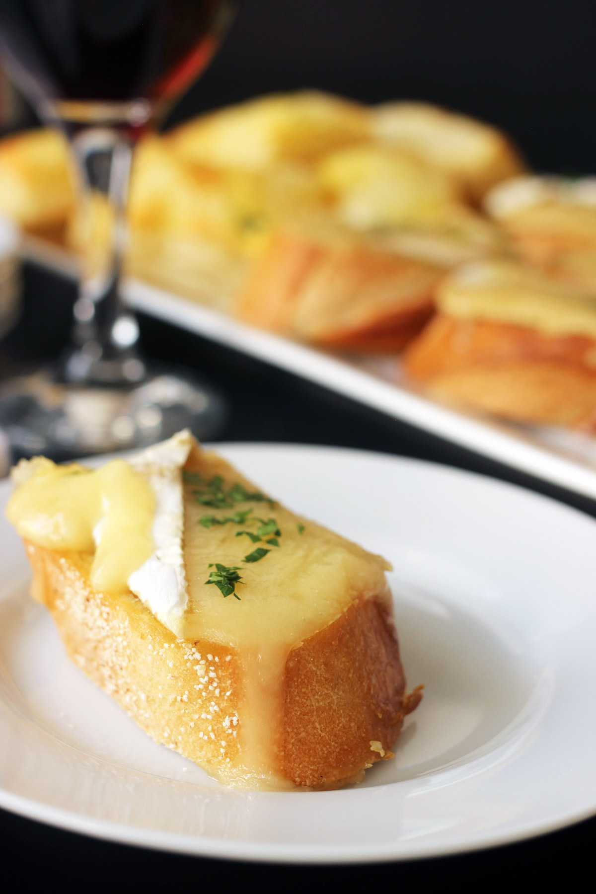 brie toast on appetizer plate next to platter