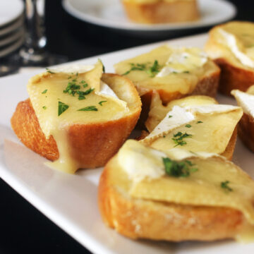 platter of brie toasts on table with wine glasses