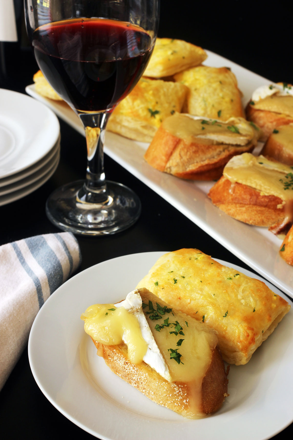 brie toast and cheese puff on plate with glass of wine