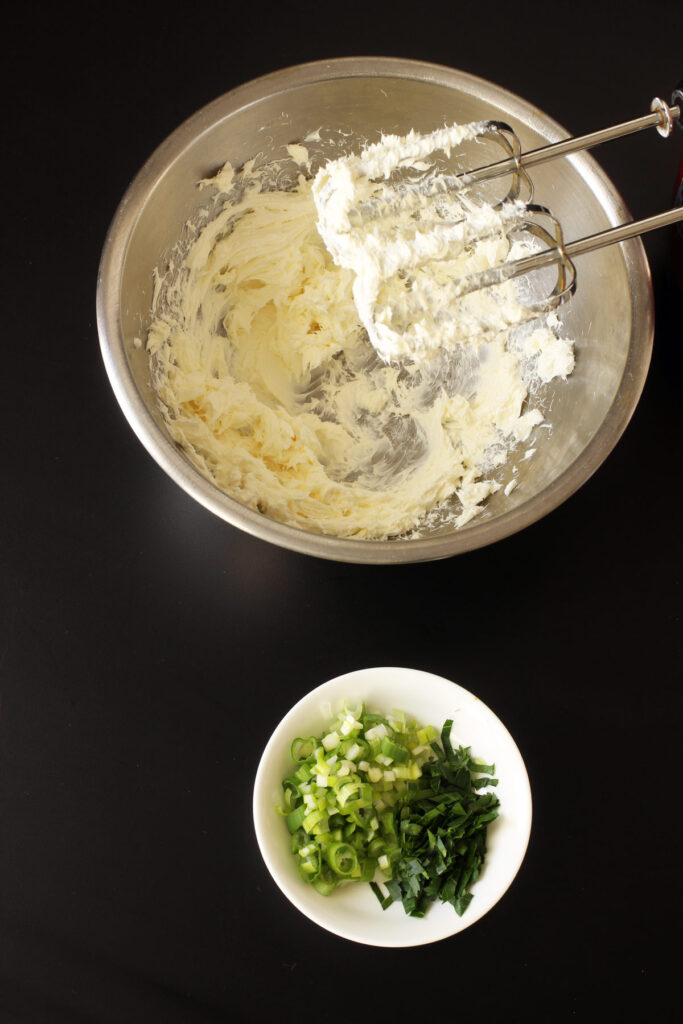 green onions and parsley next to bowl of whipped cream cheese