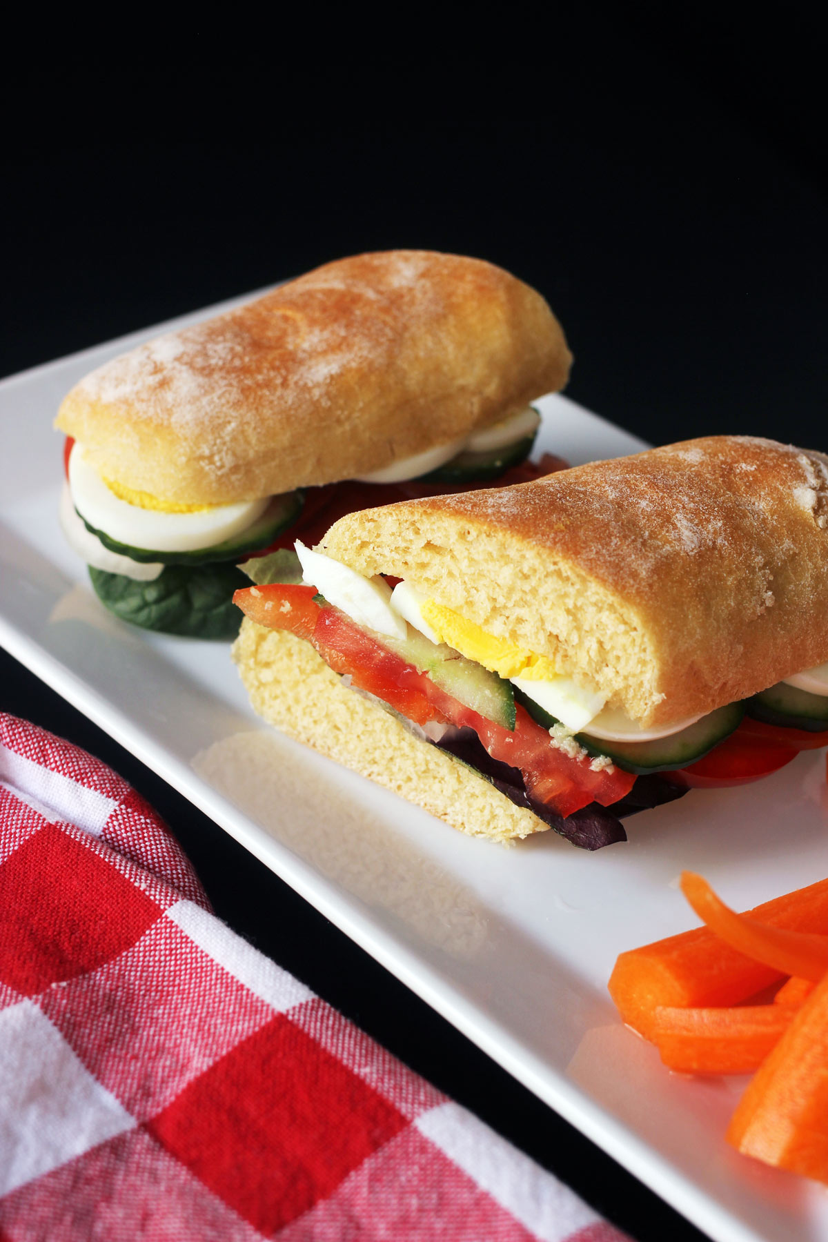 egg sandwich cut in half on platter with carrots