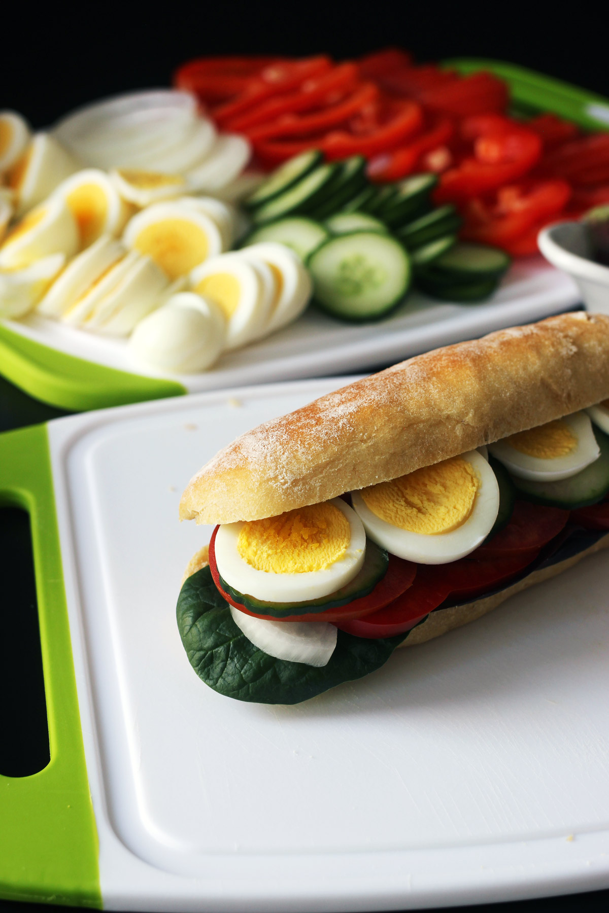 egg sandwich with lid open next to platter of fillings