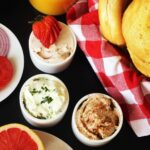 three ramekins of flavored cream cheese on bagel buffet