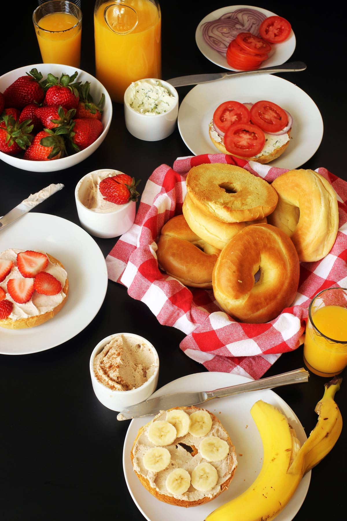 bagel buffet set on table with fruit and juice
