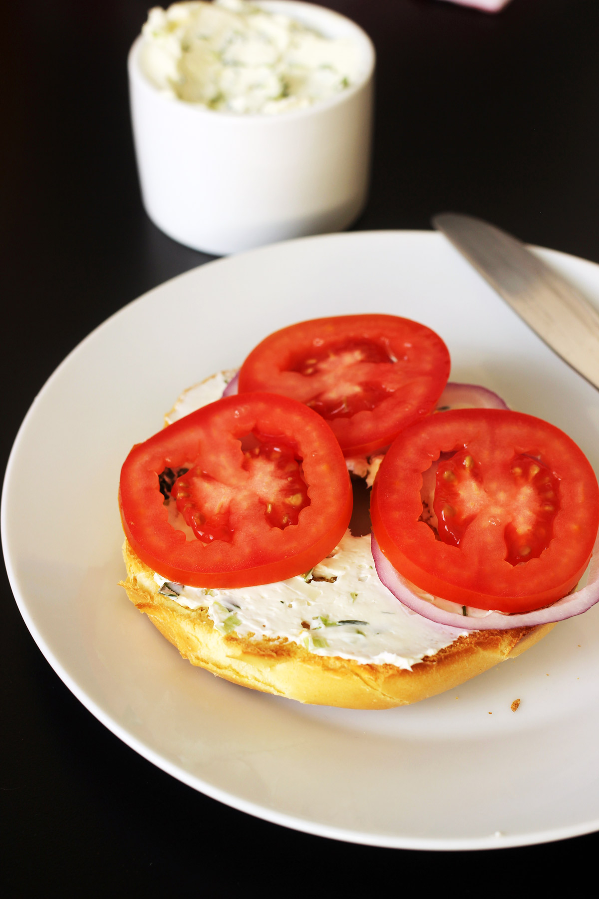 sliced tomatoes on green onion cream cheese bagel