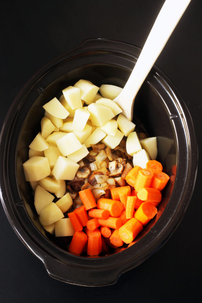 adding vegetables to slow cooker