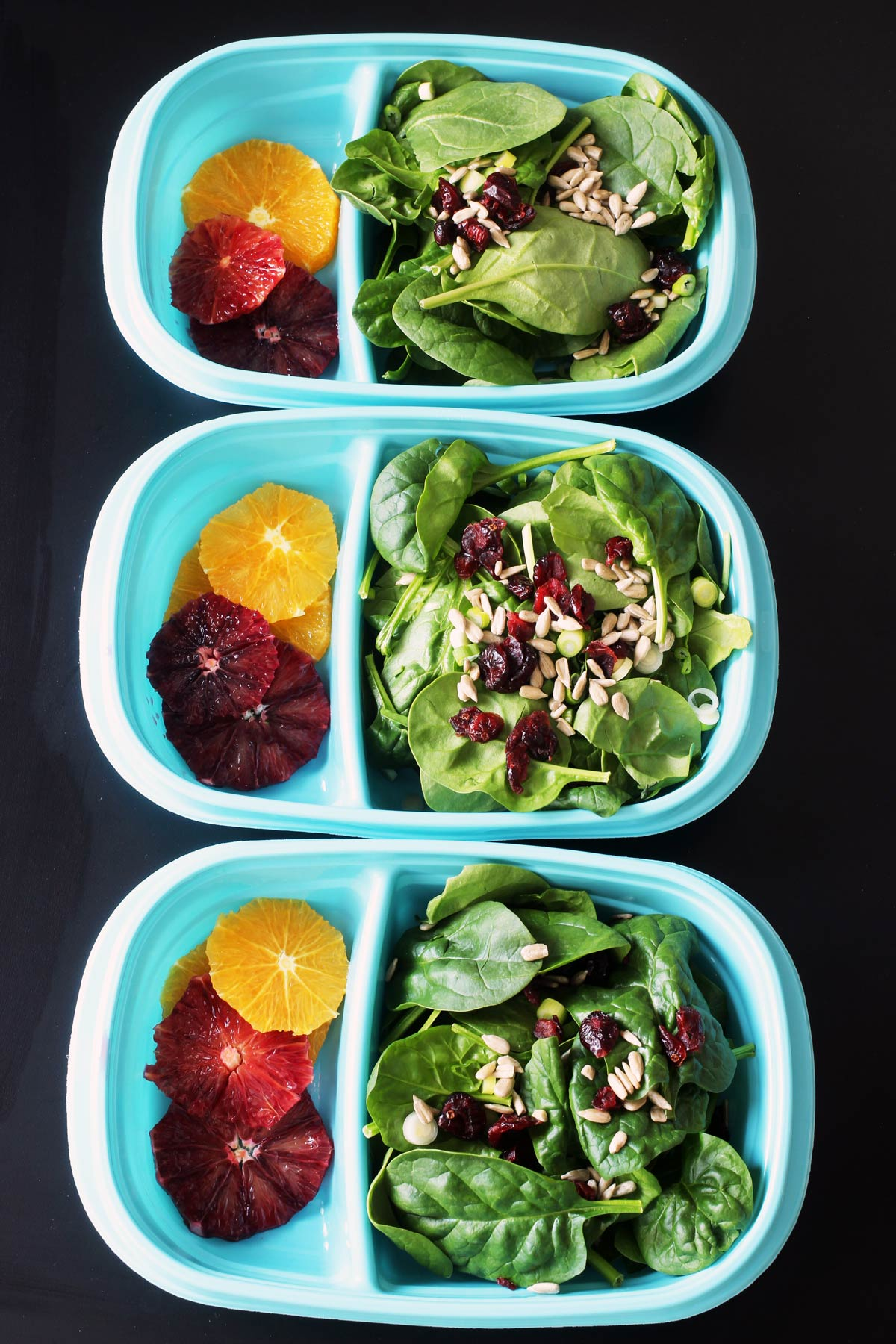 spinach salad in blue meal prep boxes